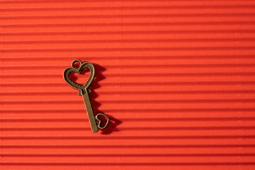 Vintage heart key on red corrugated paper background