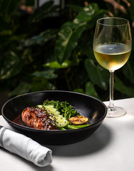 Haute cuisine - grilled salmon with asparagus and cucumbers on a side in a dark bowl outside restaurant in a summer day with a glass of white wine