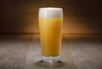 A pint of IPA, hazy unfiltered juicy draft NEIPA beer on wooden background