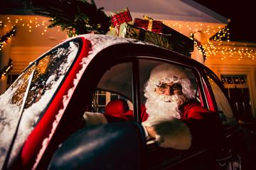 Portrait of Santa Claus. Santa Claus is driving a car