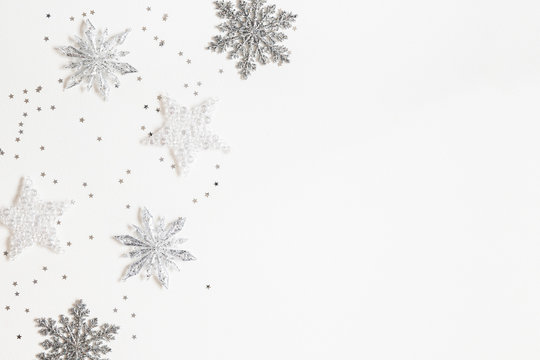 Christmas or winter composition. Frame made of silver snowflakes on white background. Christmas, winter, new year concept. Flat lay, top view, copy space