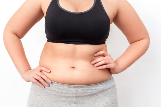Body Care. Chubby girl with bare belly standing isolated on white hands on hips close-up