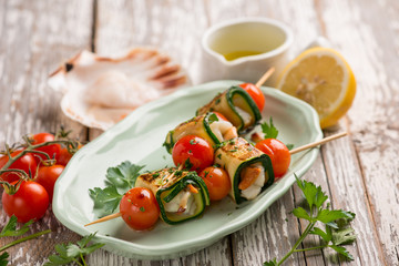 skewer rolled up with zucchinis scallop and tomatoes