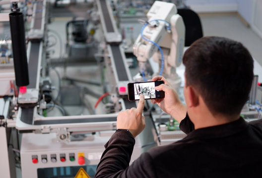 Industry 4.0 Augmented Reality concept. Man is holding smart phone and using AR service for monitoring, controlling or maintenance application with smart factory background. Selective Focus.