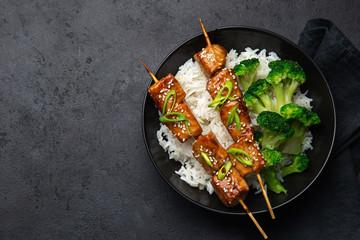 Teriyaki salmon skewers with rice and broccoli on black plate
