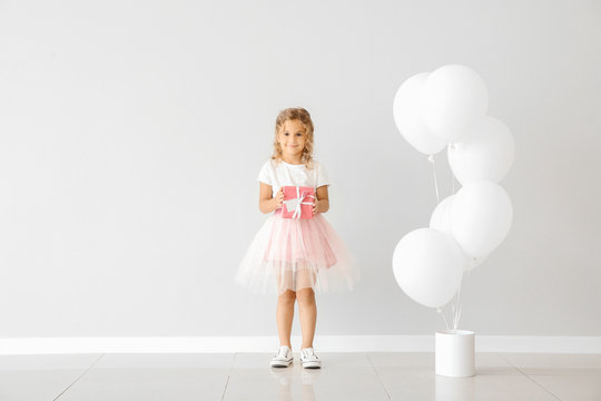 Little girl with balloons and gift near light wall