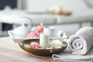 Towel, plate with flowers and candle on table in spa salon