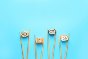 Tasty sushi rolls and chopsticks on color background