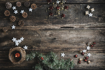 Top view of rustic wooden desk with holiday decorations, ornaments and candle placed on it