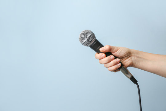 Female hand with microphone on color background