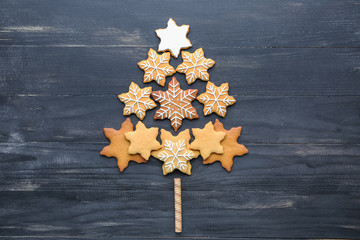 Christmas tree shape made of tasty cookies on wooden background