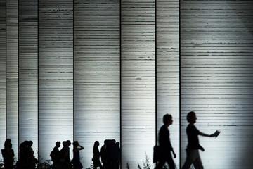 Persone in silhouette con palazzo sullo sfondo
