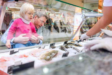 Family buying fish in the supermarket