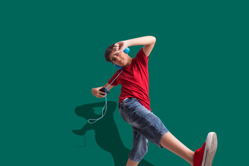 Portrait of a young boy listening to  music through headphones and dancing. (Children)