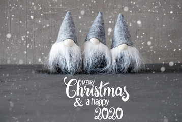 English Calligraphy Merry Christmas And A Happy 2020. Thress Santa Claus With Hat And Cement Background.