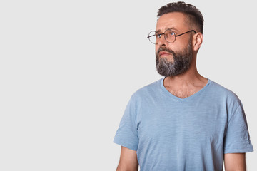 Picture of handsome bearded man wearing glasses and gray casual t shirt, posing isolated over white background in studio and looking aside. Copy space for your advertisment or promotion text.