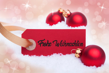 Red Label With German Frohe Weihnachten Mean Merry Christmas. Christmas Ball Ornament. Shiny Bokeh Background With Snow