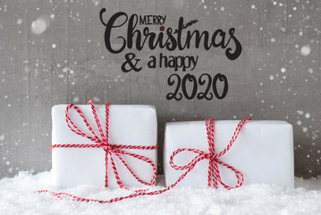 Label With English Calligraphy Merry Christmas And A Happy 2020. Two White Gifts With Red Bow. Gray Concrete Background With Snow And Snowflakes