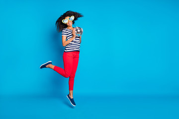 Full length turned body size photo of cheerful excited jumping girlfriend in striped t-shirt jumping with star shaped glasses isolated near empty space with disco ball vivid color blue background