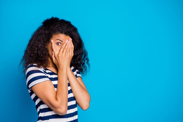 Photo of scared frightful girlfriend hiding her face to avoid negative emotions wearing striped t-shirt looking through hand near empty space isolated vivid blue color background