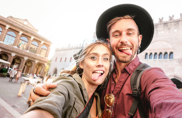 Happy boyfriend and girlfriend in love having genuine fun taking selfie at old town tour - Wanderlust life style travel vacation concept with tourist couple on city sightseeing - Bright warm filter