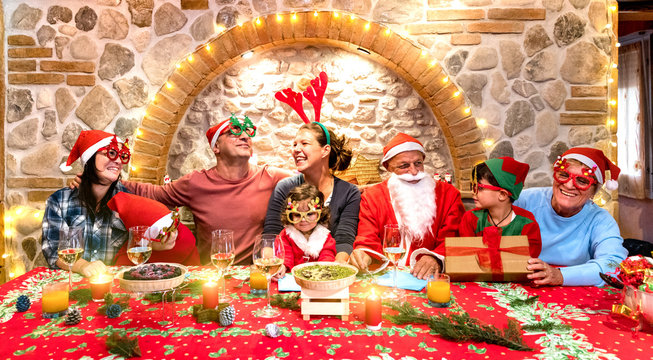 Group photo of multi generation family on santa hats clothes having fun at christmas fest house party - Winter holiday x mas concept with parents and children eating together - Warm cosy red filter