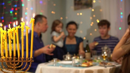 Happy Jewish family celebrates Hanukkah holiday. Hanukkah lights at home, with family and friends. Chanukah table dinner and foods. Menorah with nine burning candles in the foreground