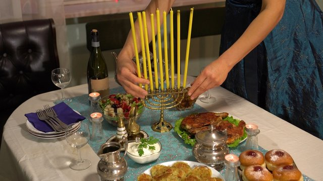 Jewish festival of lights. Latkes (potato pancakes) and sufganiyot jelly doughnuts foods cooked in oil—are customarily eaten during Hanukkah. Festive family dinner, menorah with candles