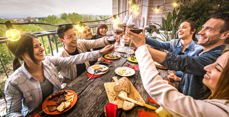 Young people having fun toasting red wine together at dinner party in outdoor villa - Happy friends eating bbq food at restaurant patio - Millennial life style concept on warm retro filter - Wide view