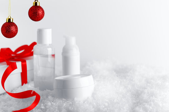 Skincare cosmetics bottles on stylized snow covered surface. White gift box with red ribbon and glittery baubles decorative background. New Year and Christmas time woman presents idea