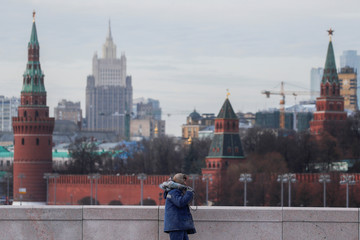 A construction worker walks along the bridge with Moscow's Kremlin in the background, in Moscow