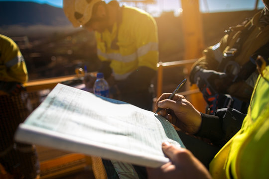 Construction miner workers signing working at height permit on open field job site prior to starting high risk work each shift construction mine site Australia