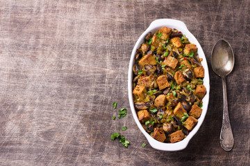 Vegan Stuffing with Mushrooms, Leeks and crunchy croutons on wooden table, top view, horizontal. Thanksgiving traditional meal