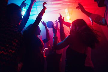 Foto op Aluminium Dance School A crowd of people in silhouette raises their hands on dancefloor on neon light background. Night life, club, music, dance, motion, youth. Purple-pink colors and moving girls and boys.