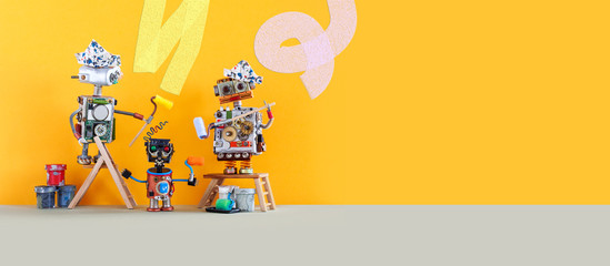 Comical robotic art. Funny toy robots house painters decorate the walls. House improvement and renovation concept. Yellow wall background, copy space