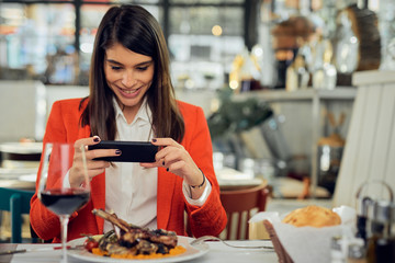 Attractive businesswoman in suit sitting in restaurant and taking picture of food over smart phone.