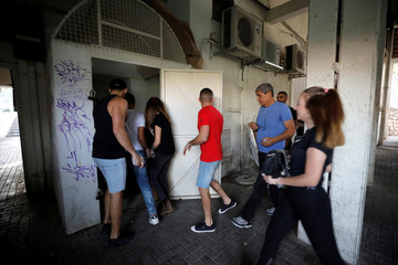 People run to take shelter as a siren warning of incoming rockets sound as a spike in cross-border violence with Gaza continues, in Ashkelon, southern Israel