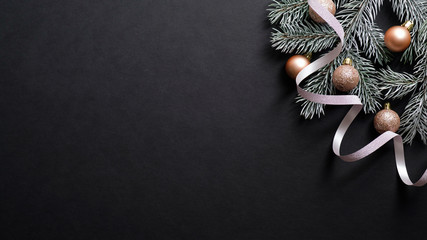 Christmas banner. Christmas tree branch decorated copper color balls and ribbon on black background. Flat lay, top view. Xmas banner mockup with copy space. Wall mural