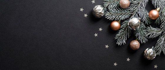 Christmas banner. Christmas tree branch decorated cooper and silver color balls on black background with confetti. Wide Xmas banner mockup, header, flyer