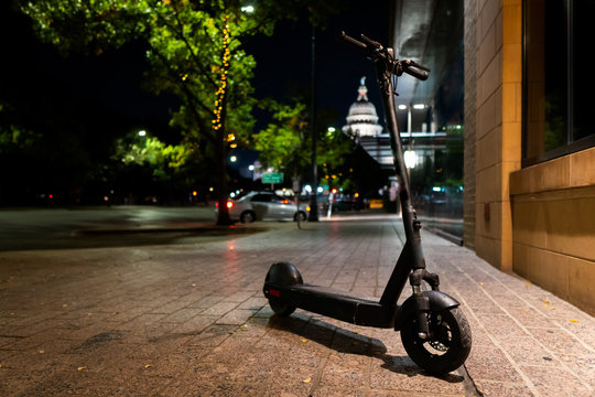 Isolated Electric Scooter parked on the sidewalk in Front of Capitol building in Austin highlighting micro mobility, electric scooter isolated
