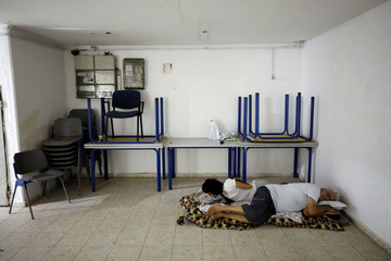 People rest on the floor inside a bomb shelter as a spike in cross-border violence with Gaza continues, in Ashkelon, southern Israel