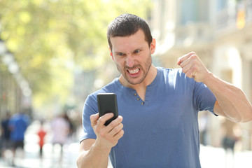 Angry man checking crashed smart phone in the street