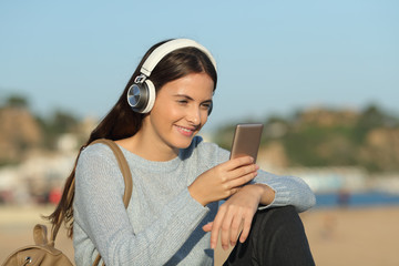 Happy girl listens to music with headphones and mobile phone