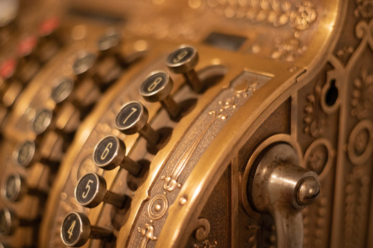 Close up picture of an antique bronze cash register with red, white, and black buttons or keys, with top of handle in image.