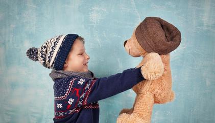 niedlicher Junge kuschelt mit Teddy