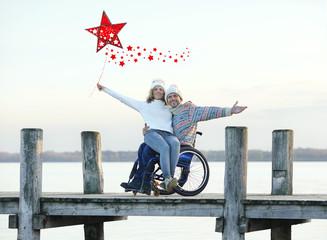 Weihnachten feiern - Rollstuhfahrer mit Partnerin am See