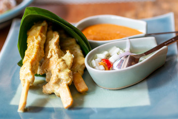 Chicken satay wrapped in banana leaf. Close up of three sticks chicken satay with dipped sauce.  Picture of halal chicken appetizer served on a ceramic plate. Delicious Asian Cuisine Chicken Satay.