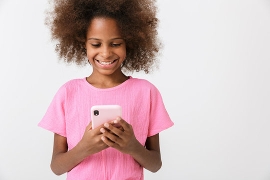 Happy young african girl kid using mobile phone.