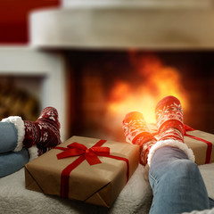 Woman legs with christmas woolen socks and home interior with fireplace.Free space for your...