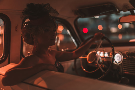 Portrait of beautiful sexy fashion blond girl. Model with bright makeup and curly hairstyle in retro style hat sitting in old car. Attractive woman  rides around the night city